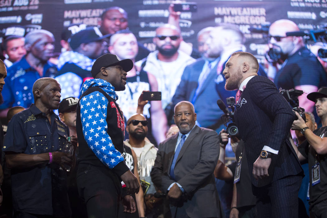 Boxer Floyd Mayweather Jr., left, and UFC fighter Conor McGregor, during a world tour event stop to promote their upcoming fight, at Staples Center in Los Angeles, Calif., on Tuesday, July 11, 201 ...
