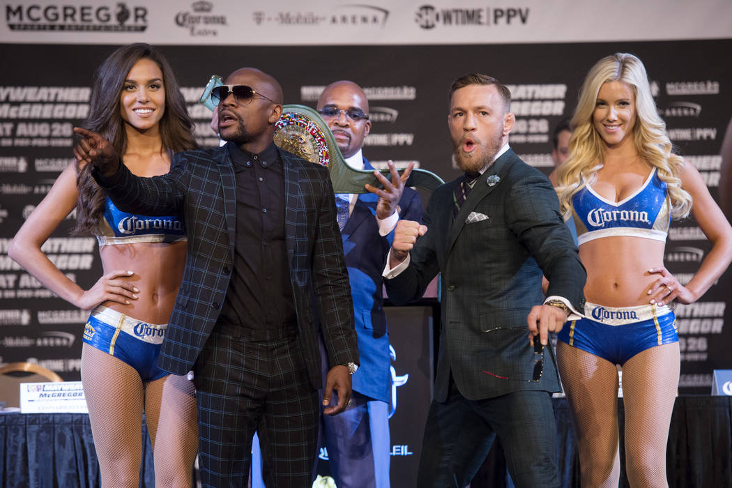 Floyd Mayweather tells one of his fans to quiet down while Conor McGregor poses during the final news conference Wednesday, Aug. 23, 2017, at the MGM Grand before their scheduled Aug. 26 fight. Sa ...