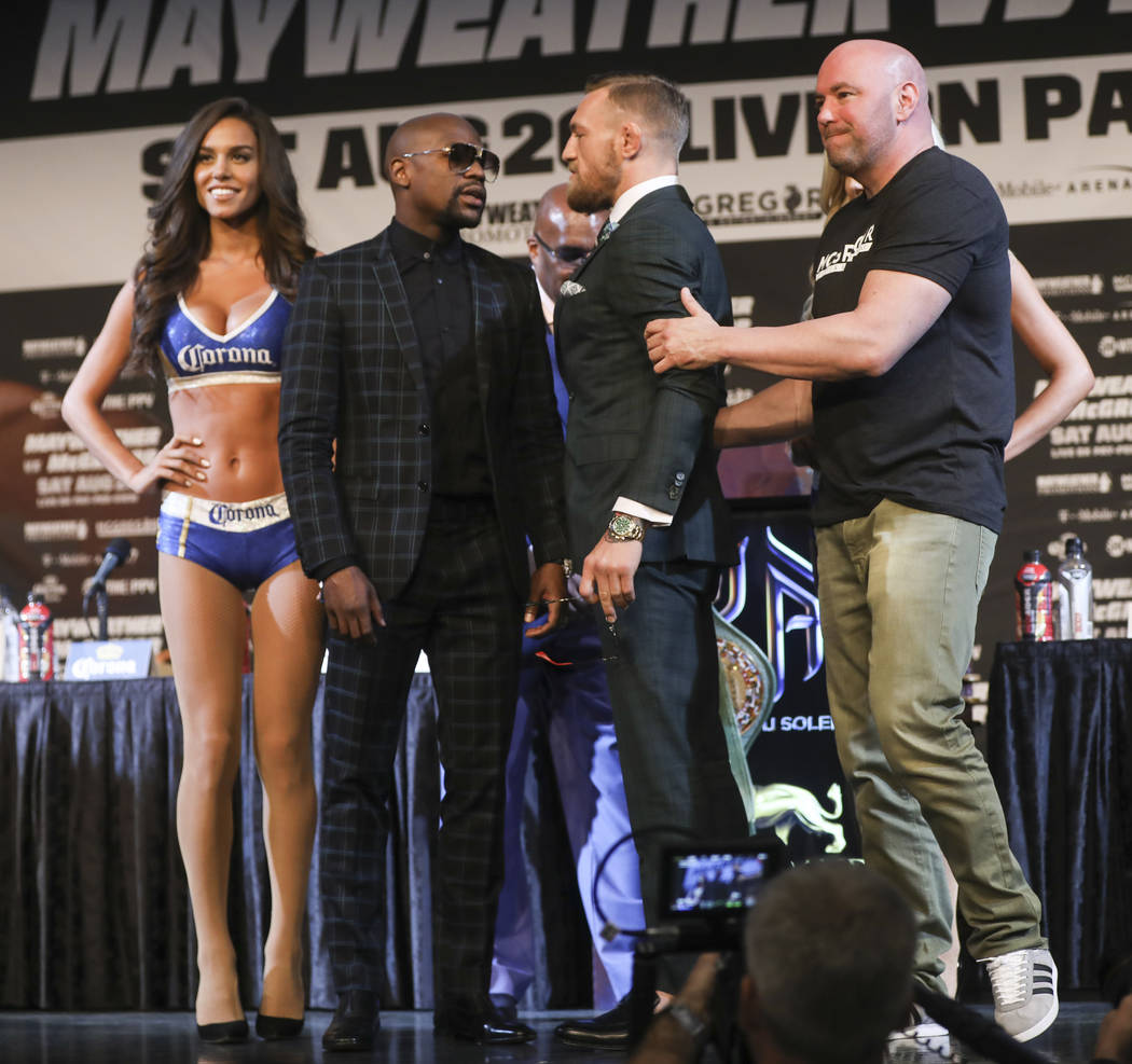 Floyd Mayweather Jr., left, and Conor McGregor face off during the final press conference ahead of their fight, slated for Aug. 26 at the T-Mobile Arena, as UFC President Dana White holds McGregor ...