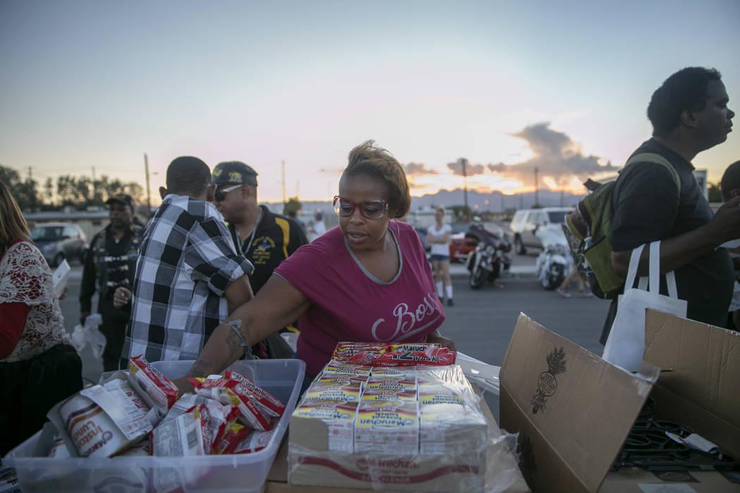 "A woman who preferred to go by ""Nene"" reaches for some instant ramen at the Homeless Lives Matter free dinner in slain homeless man Daniel Aldape's memory, Thursday, Aug. 24,  2017, in Las Vegas.  ..."