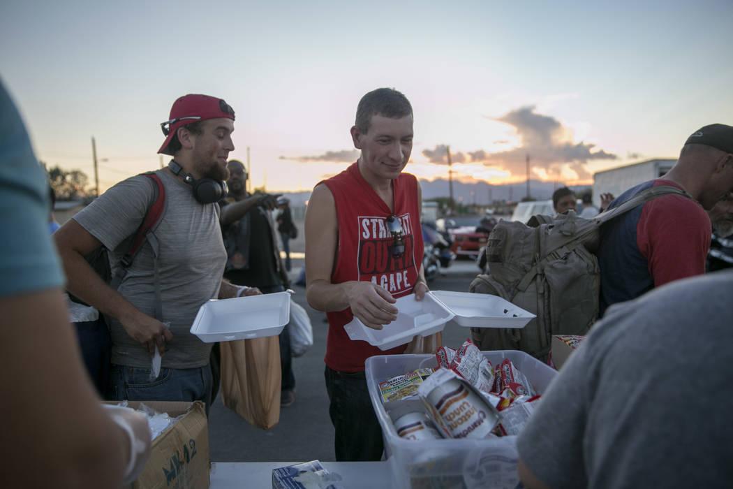James Corbin Jr. of Las Vegas, from left, and Jason Rohdy, a Las Vegas resident originally from Ohio get dinner during the Homeless Lives Matter free dinner in slain homeless man Daniel Aldape's m ...