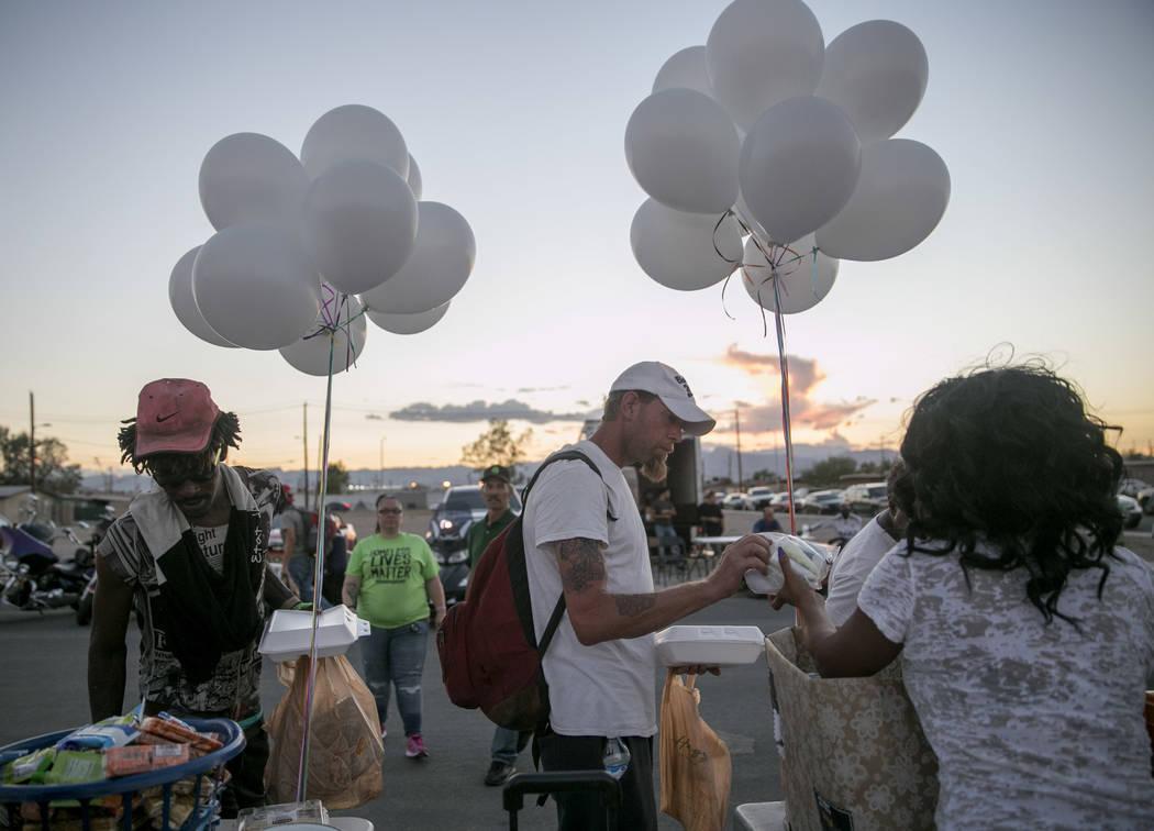 People accept free dinner and toiletries during the Homeless Lives Matter free dinner in slain homeless man Daniel Aldape's memory, Thursday, Aug. 24, 2017, in Las Vegas. Gabriella Angotti-Jones L ...