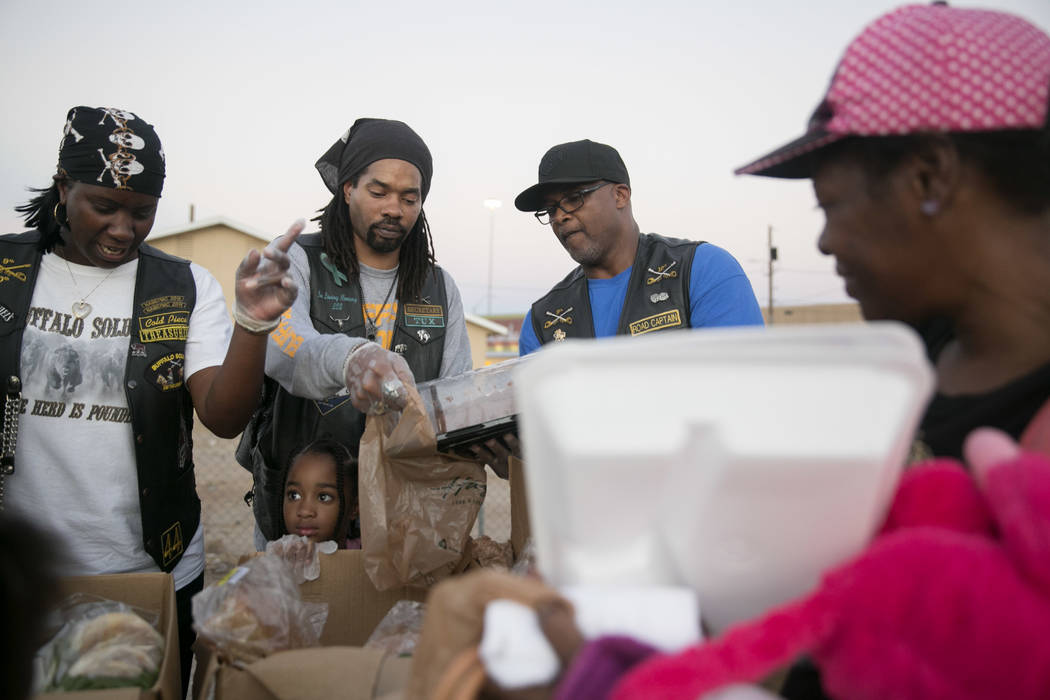 """Melissa """"Cold Piece"""" Wesley, from left, Caedence """"Sweet Pea"""" Simmons, her father Scott """"Tux"""" Simmons and Rodney """"Gambler"""" Anderson pass out food during the Homeless Lives Matter free dinner in sla ..."""