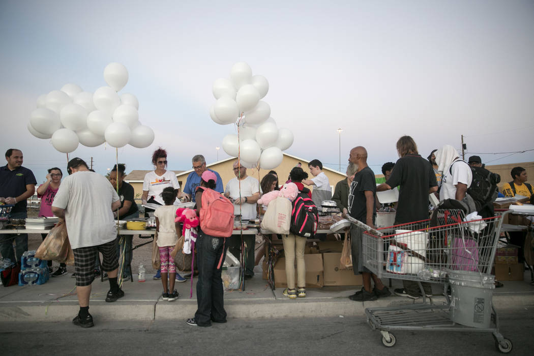 People collect free food, clothes, and toiletries from volunteers during the Homeless Lives Matter free dinner in slain homeless man Daniel Aldape's memory, Thursday, Aug. 24, 2017, in Las Vegas.  ...