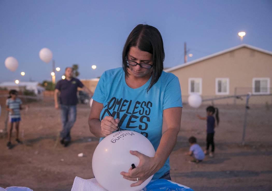 """Keely Schalk, sister of slain homeless man Daniel Aldape, writes """"Missing You Daniel"""" on a balloon during the Homeless Lives Matter free dinner in Aldape's memory, Thursday, Aug. 24,  2017, in Las ..."""