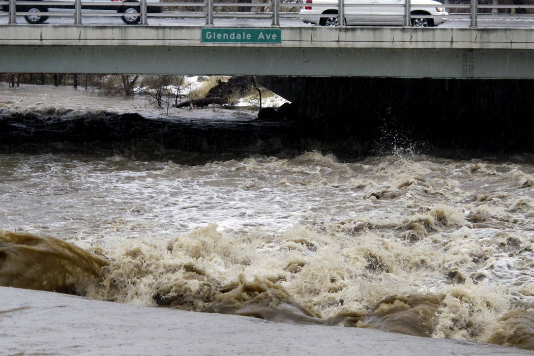 Traffic crosses the raging Truckee River, Sunday, Jan. 8, 2017, where it runs near the Grand Sierra hotel-casino along a line that divides the cities of Reno and Sparks, Nevada. More than 1,000 ho ...