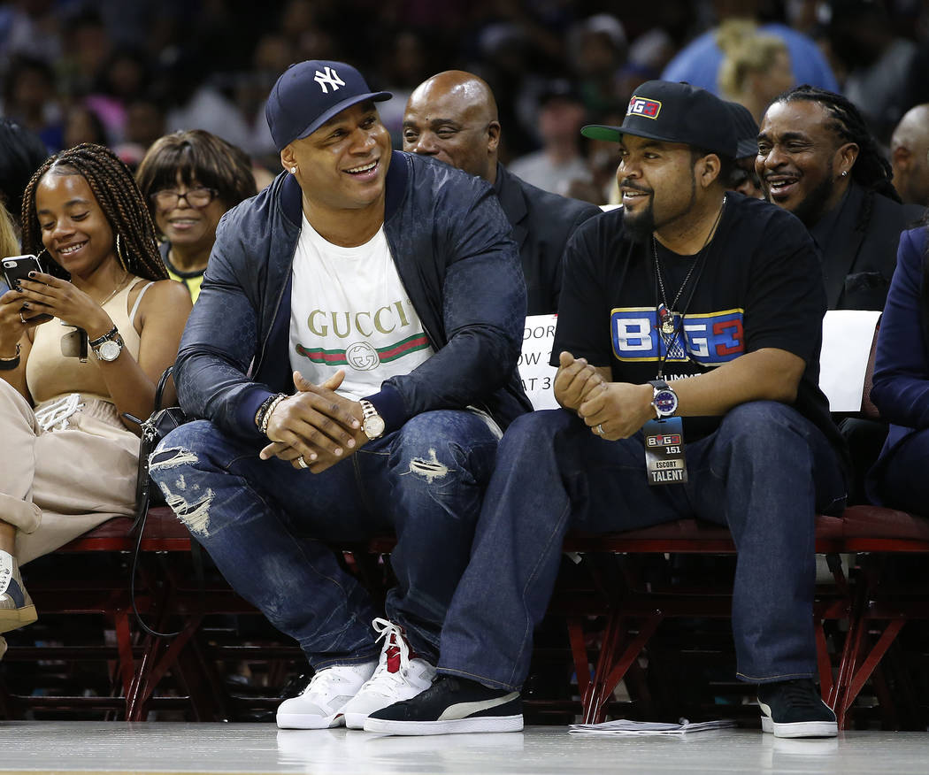 LL Cool J, second from front left, and Ice Cube watch the action as The Power plays the Ghost Ballers during the first half of Game 1 in the BIG3 Basketball League in Philadelphia, Pa., Sunday, Ju ...