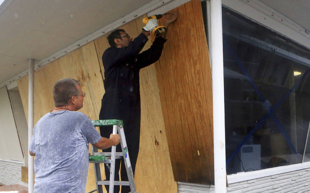 Vimal Patel  boards up windows with the help of Carl Bledsoe, left, at the Catalina Motel as Hurricane Harvey approaches the Coastal Bend area on Friday, Aug. 25, 2017, in Corpus Christi, Texas. ( ...