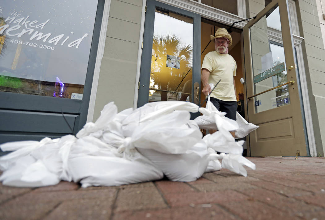 Lynn Dixon places sandbags outside their home decor store in Galveston, Texas as Hurricane Harvey intensifies in the Gulf of Mexico Friday, Aug. 25, 2017. (David J. Phillip/AP)