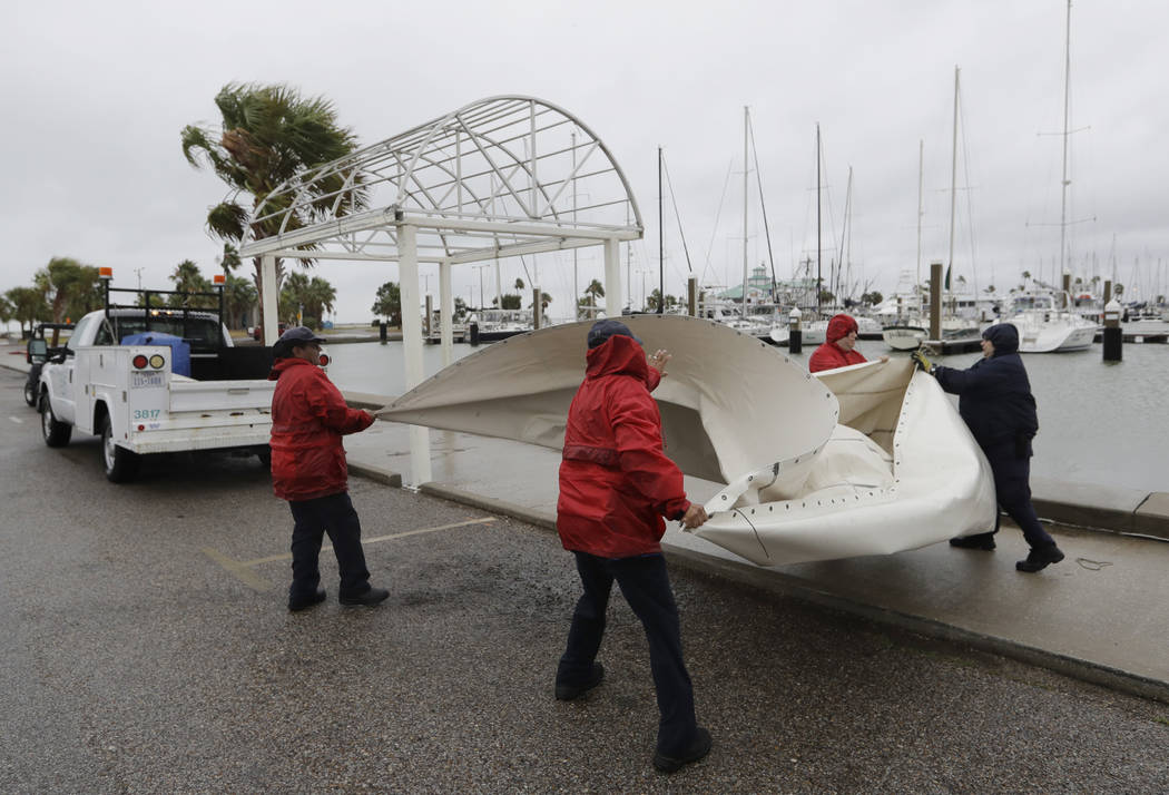 City workers pull down a canvas covering as the outer bands of Hurricane Harvey move closer, Friday, Aug. 25, 2017, in Corpus Christi, Texas.  The National Hurricane Center warns that conditions a ...