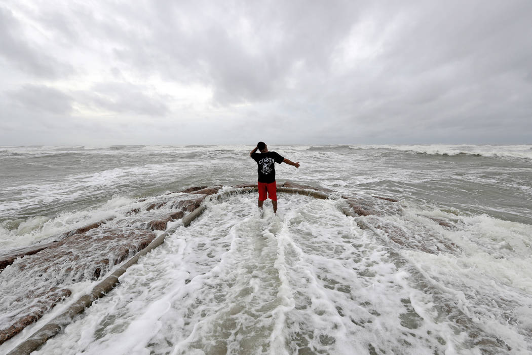 Luis Perez watches waves crash again a jetty in Galveston, Texas as Hurricane Harvey intensifies in the Gulf of Mexico Friday, Aug. 25, 2017. Harvey is forecast to be a major hurricane when it mak ...