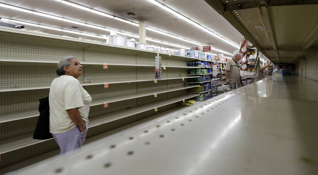 Shoppers pass empty shelves along the bottled water aisle in a Houston grocery store as Hurricane Harvey intensifies in the Gulf of Mexico, Thursday, Aug. 24, 2017. Harvey is forecast to be a majo ...