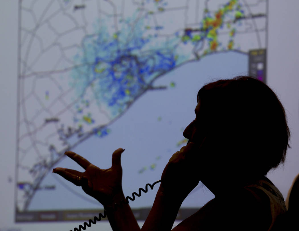 A map of the Texas Coast is projected on a screen as Deb Nowinski, a disability integration coordinator, gives information to a caller regarding the approach of Hurricane Harvey at the Galveston C ...