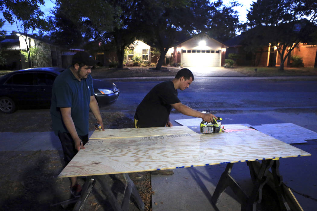 Mauro Eligio, left, gets help boarding up his home from his neighbor Chris Baker on the Southside of Corpus Christi, Texas on Thursday, Aug. 24, 2017, in advance of Hurricane Harvey.  (Rachel Denn ...