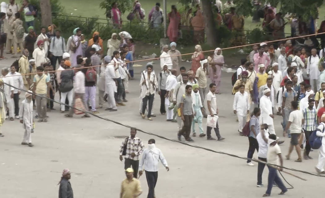 In this image made from video, supporters of an Indian guru who calls himself Saint Dr. Gurmeet Ram Rahim Singh Ji Insaan walk in the street as they react after his verdict was announced in Panchk ...
