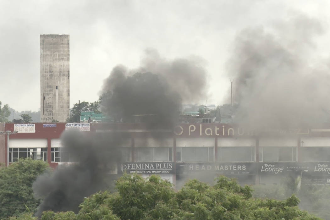 In this image made from video, smoke rises as supporters of an Indian guru who calls himself Saint Dr. Gurmeet Ram Rahim Singh Ji Insaan react after his verdict was announced in Panchkula, India,  ...