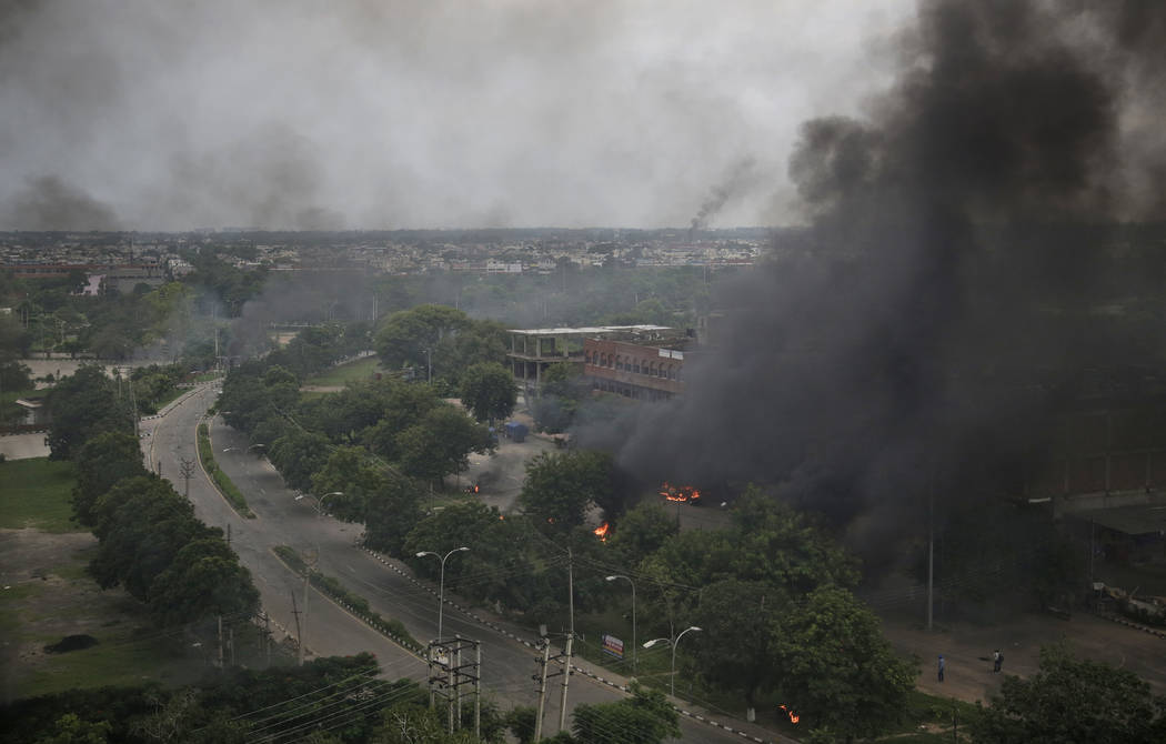 Smoke billows after supporters of the Dera Sacha Sauda sect set vehicles on fire near in Panchkula, India, Friday, Aug. 25, 2017.  Deadly riots have broken out in a north Indian town after a court ...