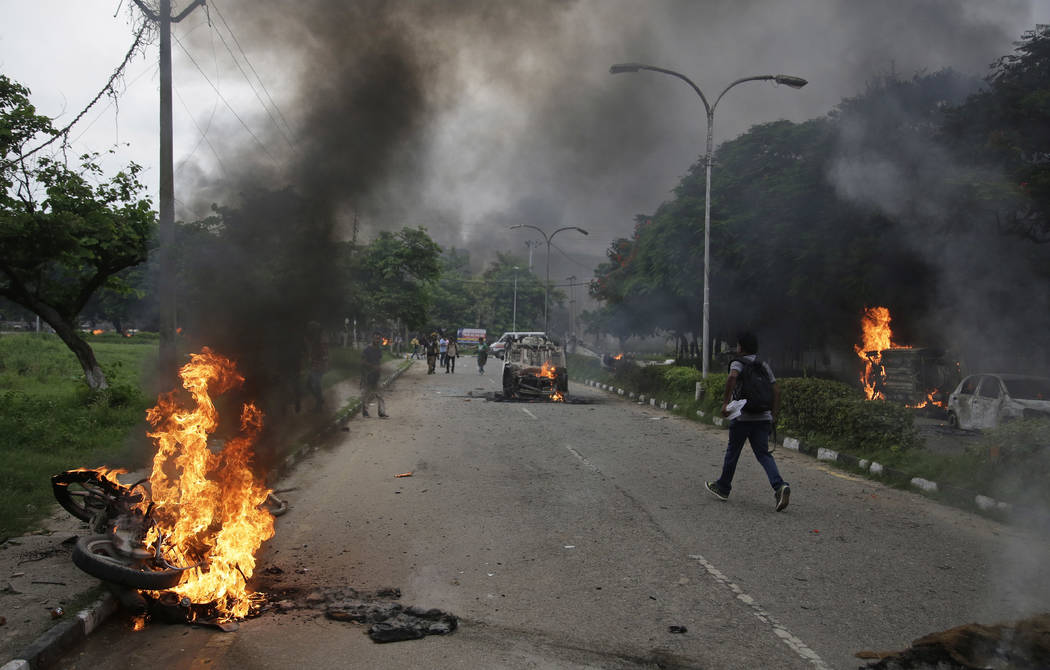 Vehicles set alight by Dera Sacha Sauda sect members burn in the streets of in Panchkula, India, Friday, Aug. 25, 2017. Deadly riots have broken out in a north Indian town after a court convicted  ...