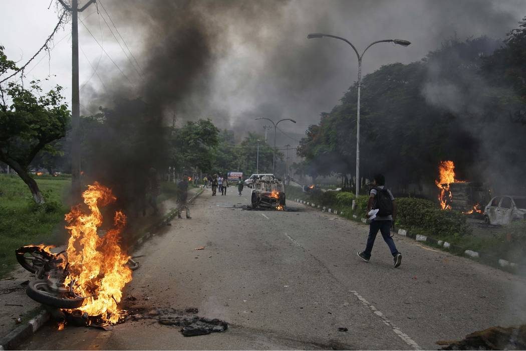 Vehicles set on fire by Dera Sacha Sauda sect members burn in the streets of in Panchkula, India, Friday, Aug. 25, 2017. Deadly riots have broken out in a north Indian town after a court convicted ...