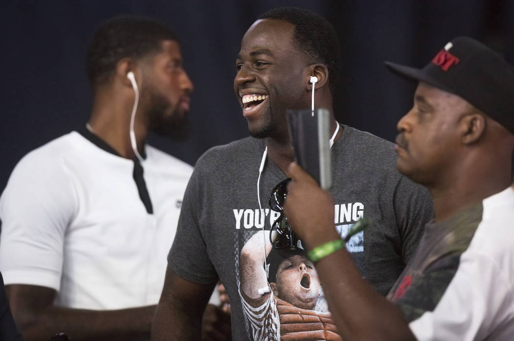 Golden State Warriors power forward Draymond Green, middle, jokes around with the crowd during weigh-ins for Saturday's Mayweather McGregor fight on Friday, Aug 25, 2017, at T-Mobile Arena, in Las ...