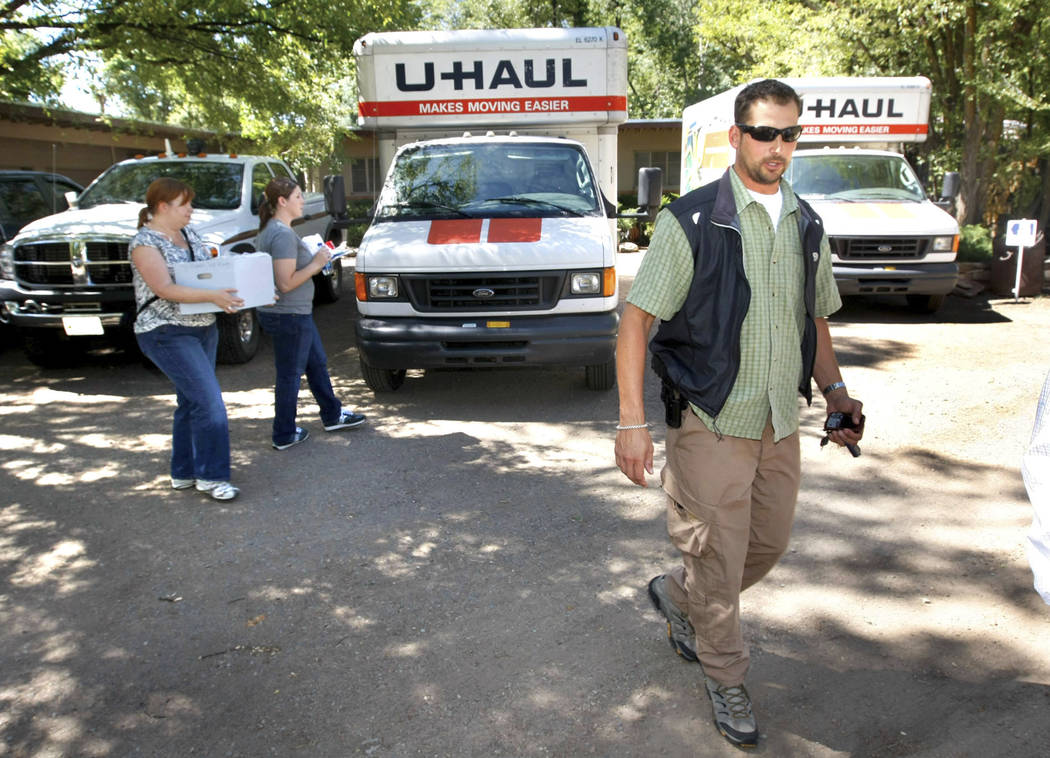 """Daniel Love, a special agent with the Bureau of Land Management, walks in front of Carl """"Vern"""" Crites' home in Durango Colo., on Aug. 19, 2009, after Crites voluntarily turned over his entire coll ..."""