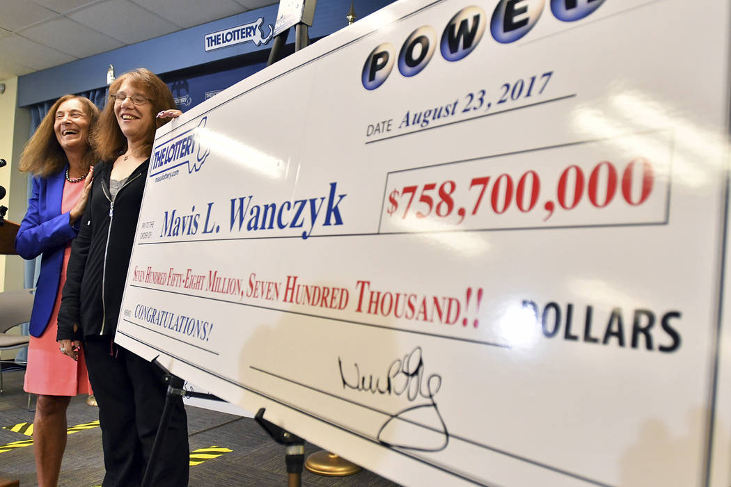 Mavis Wanczyk, of Chicopee, Mass., stands by a poster of her winnings during a news conference where she claimed the $758.7 million Powerball prize at Massachusetts State Lottery headquarters, Thu ...
