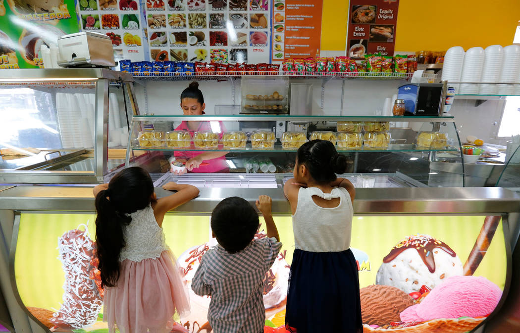 Angelina Gonzalez, 6, from left, her brother Julius, 3, and her sister Vianna, 7, watch their mother Nayeli, background, working at their grandmother's shop, La Flor de Michoacan,  in Las Vegas, S ...