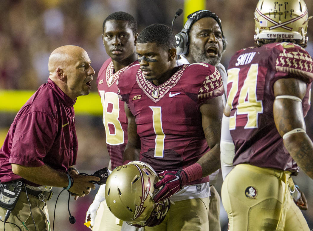File-This Sept. 20, 2014, file photo shows Florida State defensive coordinator Charles Kelly, left, talking to defensive back Tyler Hunter in the second half of an NCAA college football game again ...