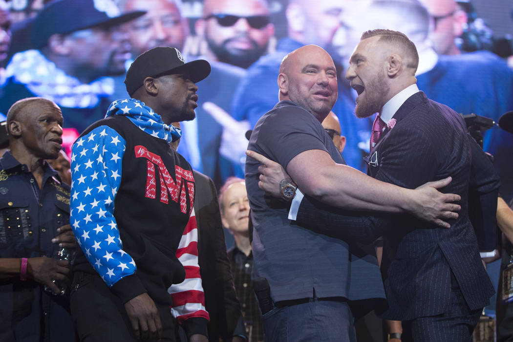 Boxer Floyd Mayweather Jr., left, and UFC fighter Conor McGregor, right, with UFC president Dana White, during a press conference in their world boxing tour to promote their upcoming fight, at Sta ...