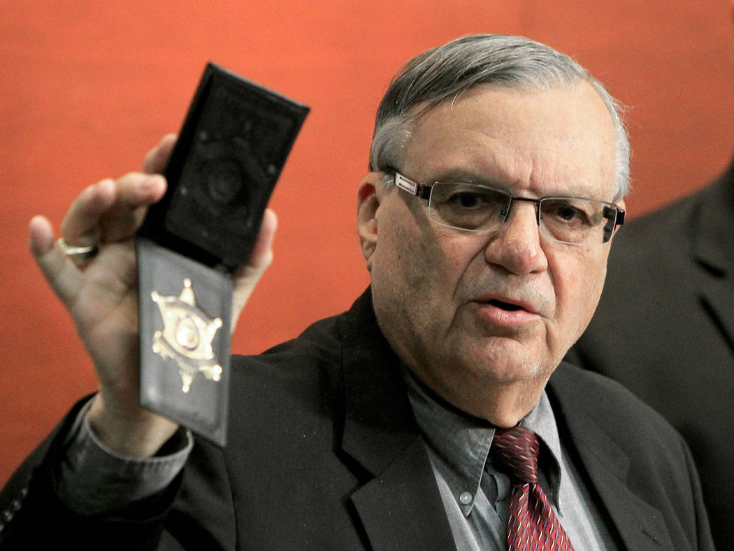 Maricopa County Sheriff Joe Arpaio shows his badge as he holds a ceremony where 92 of his immigration jail officers, who lost their federal power to check whether inmates are in the county illegal ...