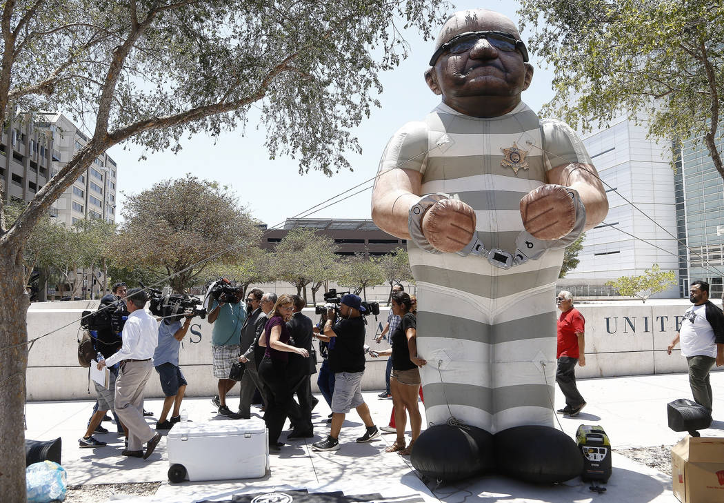 With a larger-than-life inflatable Joe Arpaio set up by protesters, members of the media follow former Maricopa County Sheriff Arpaio as he leaves U.S. District Court on the first day of his conte ...