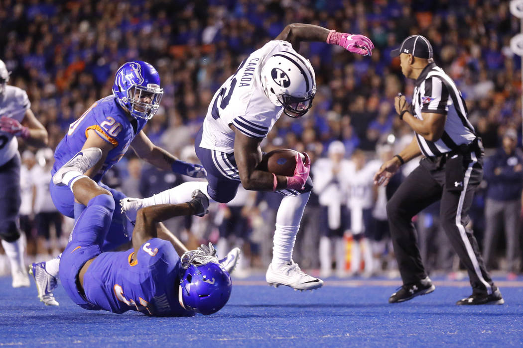 FILE - In this Oct. 20, 2016, file photo, BYU running back Squally Canada (22) is tripped up by Boise State safety Chanceller James (3) during the second half of an NCAA college football game in B ...