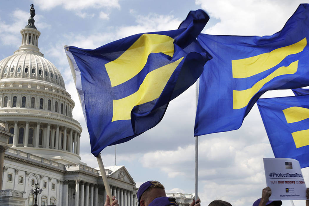 "People with the Human Rights Campaign hold up ""equality flags"" during an event on Capitol Hill in Washington, in support of transgender members of the military. (AP Photo/Jacquelyn Martin)"