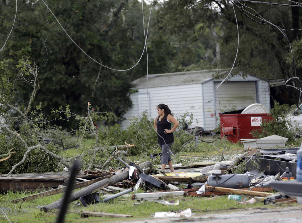 Jennifer Bryant looks over the debris where her family business once stood in the aftermath of Hurricane Harvey Saturday, Aug. 26, 2017, in Katy, Texas.  Harvey rolled over the Texas Gulf Coast on ...