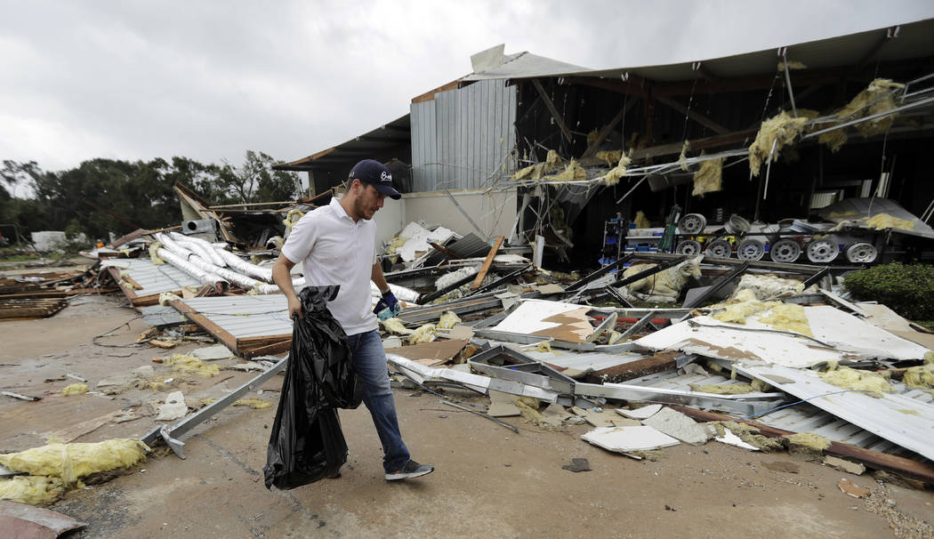 Miguel Debernardis cleans up debris in the aftermath of Hurricane Harvey Saturday, Aug. 26, 2017, in Katy, Texas.   Harvey rolled over the Texas Gulf Coast on Saturday, smashing homes and business ...
