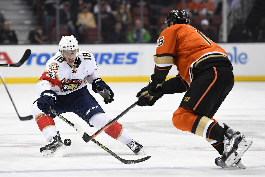 Florida Panthers right wing Reilly Smith, left, and Anaheim Ducks center Ryan Getzlaf reach for the puck during the first period of an NHL hockey game, Friday, Feb. 17, 2017, in Anaheim, Calif. (A ...