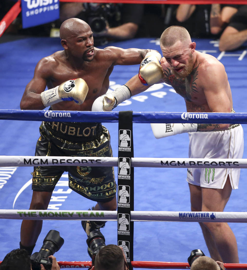 Floyd Mayweather Jr., left, delivers the final blows to Conor McGregor in their super welterweight fight at T-Mobile Arena, Saturday, Aug. 26, 2017, in Las Vegas. Mayweather won via 10th round tec ...