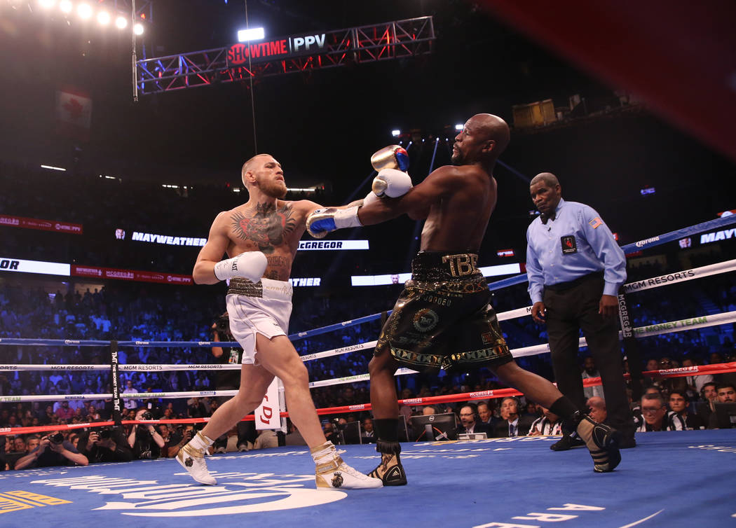 Conor McGregor takes a swing at Floyd Mayweather Jr. during the first round of their fight at T-Mobile Arena, Saturday, Aug. 26, 2017, in Las Vegas. Benjamin Hager Las Vegas Review-Journal