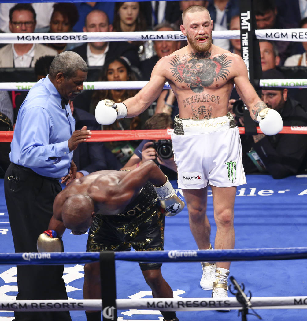 Floyd Mayweather Jr., bottom, fights Conor McGregor in their super welterweight fight at T-Mobile Arena, Saturday, Aug. 26, 2017, in Las Vegas. Mayweather won via 10th round technical knockout. Ch ...