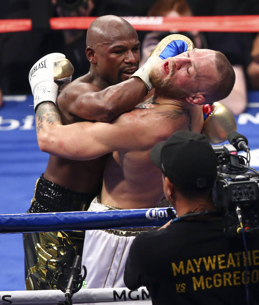 Floyd Mayweather Jr., left, fights Conor McGregor in their super welterweight fight at T-Mobile Arena, Saturday, Aug. 26, 2017, in Las Vegas. Mayweather won via 10th round technical knockout. Chas ...