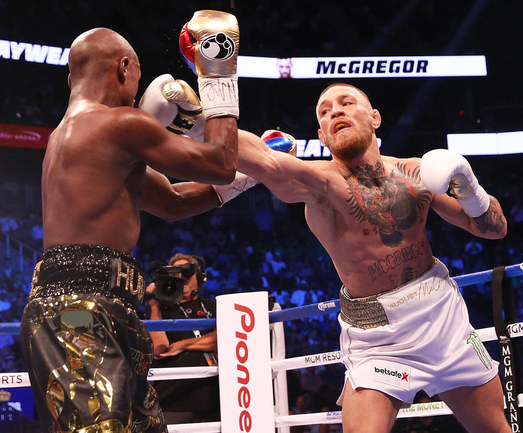 Conor McGregor, right, lands a punch against Floyd Mayweather Jr. in the blank round on Saturday, Aug 26, 2017, at T-Mobile Arena, in Las Vegas. Benjamin Hager Las Vegas Review-Journal @benjaminhphoto