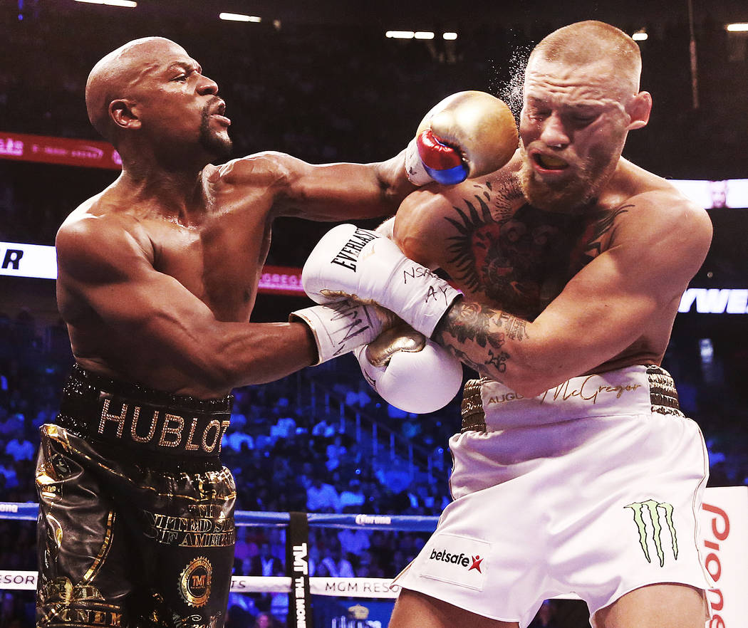 Floyd Mayweather, left, lands a punch against Conor McGregor in the blank round on Saturday, Aug 26, 2017, at T-Mobile Arena, in Las Vegas. Benjamin Hager Las Vegas Review-Journal @benjaminhphoto
