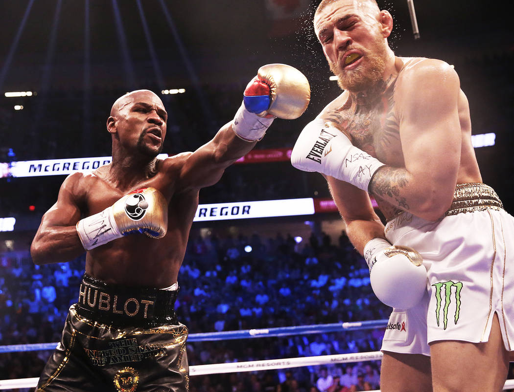 Floyd Mayweather, left, lands a punch against Conor McGregor in the 4th round on Saturday, Aug 26, 2017, at T-Mobile Arena, in Las Vegas. Benjamin Hager Las Vegas Review-Journal @benjaminhphoto