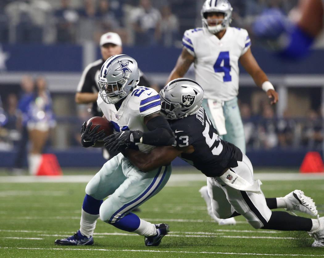 Dallas Cowboys running back Ezekiel Elliott (21) fights for extra yardage as Oakland Raiders linebacker Jelani Jenkins (53) makes the stop in the first half of a preseason NFL football game, Satur ...