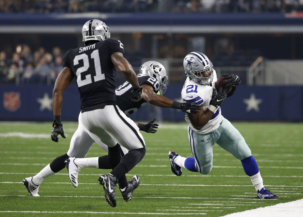 Oakland Raiders cornerback Sean Smith (21) and Obi Melifonwu (20) chase Dallas Cowboys running back Ezekiel Elliott (21) out of bounds in the first half of a preseason NFL football game, Saturday, ...