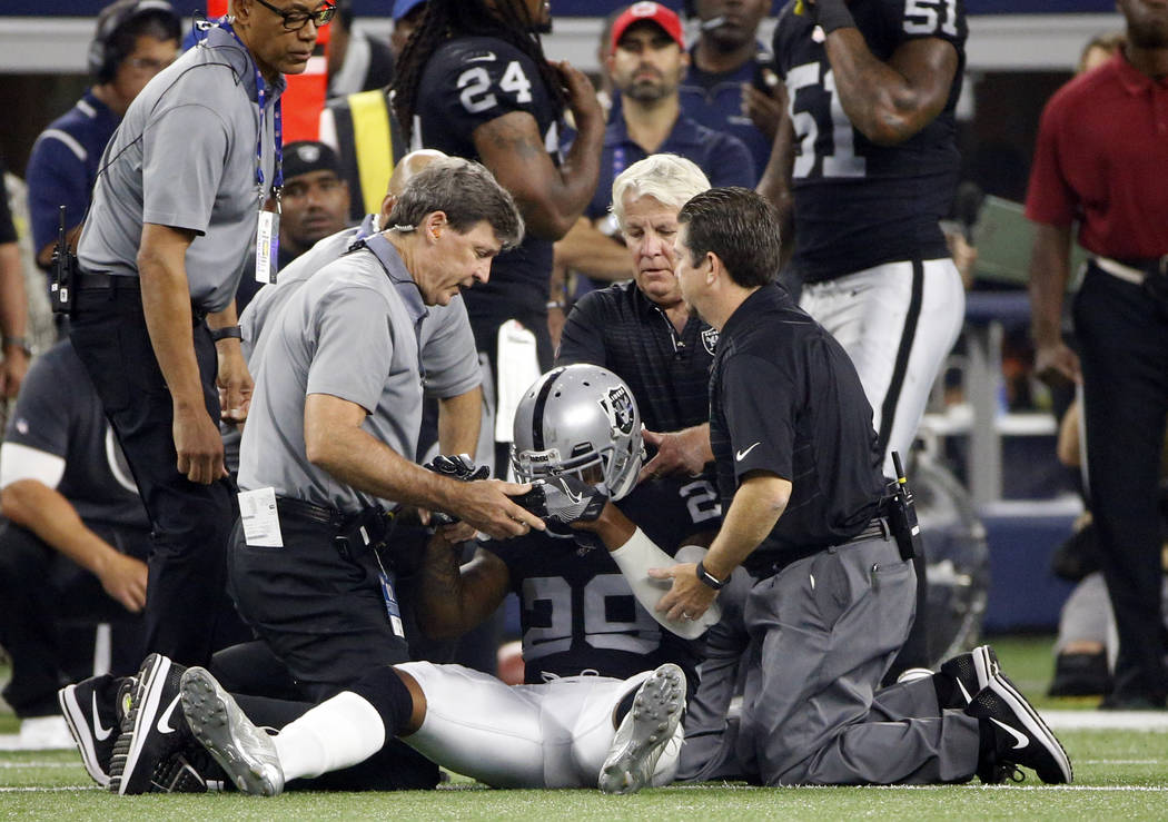 Oakland Raiders cornerback David Amerson (29) is checked on by team medical staff after suffering an unknown injury in the first half of a preseason NFL football game against the Dallas Cowboys on ...