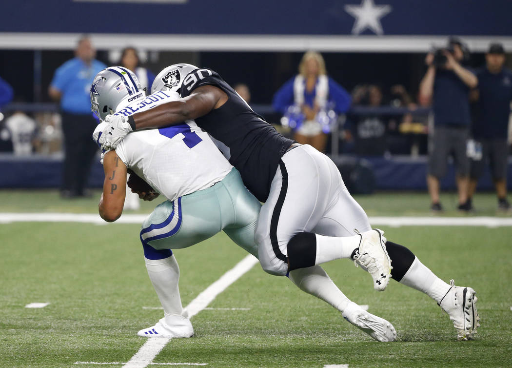 Dallas Cowboys quarterback Dak Prescott (4) is sacked by Oakland Raiders defensive tackle Treyvon Hester (90) in the first half of a preseason NFL football game, Saturday, Aug. 26, 2017, in Arling ...