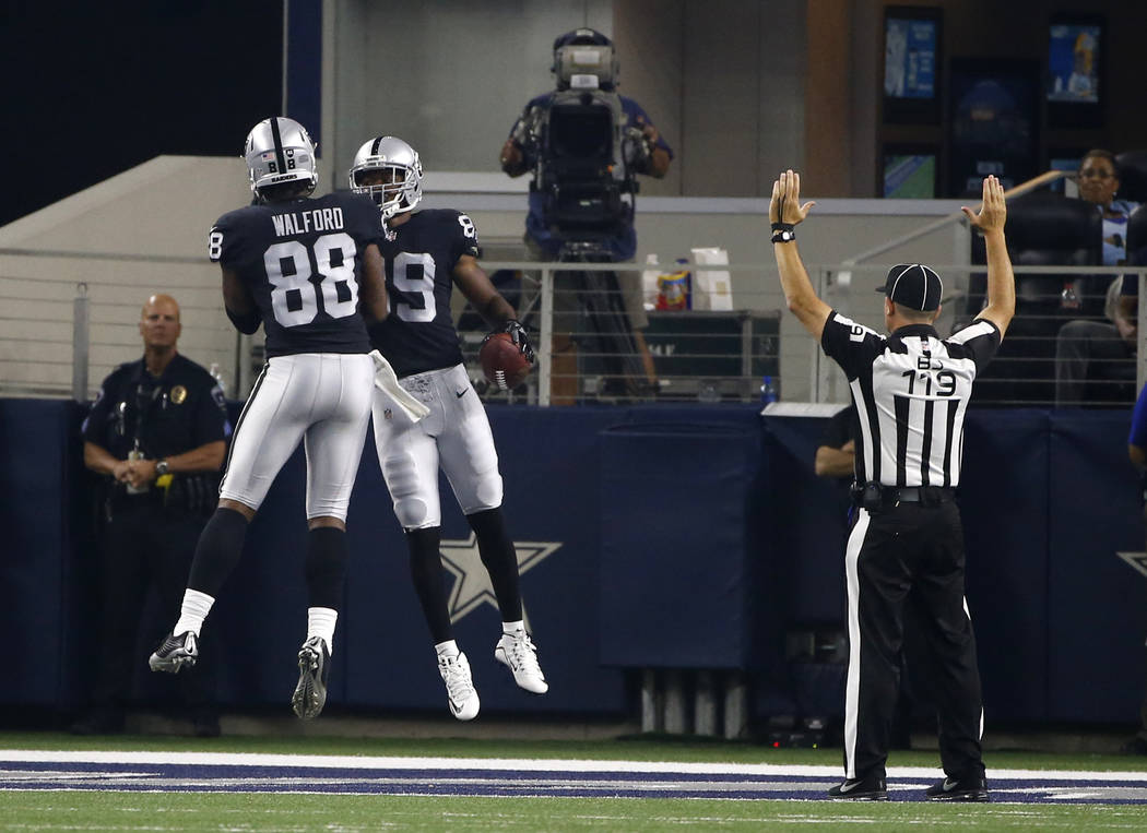 Oakland Raiders' Clive Walford (88) and Amari Cooper (89) celebrate a touchdown catch by Cooper as back judge Greg Wilson (119) signals after the play in the first half of a preseason NFL football ...