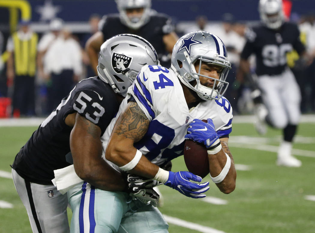 Oakland Raiders linebacker Jelani Jenkins (53) attempts the stop as Dallas Cowboys tight end James Hanna (84) fights for extra yardage after catching a pass in the second half of a preseason NFL f ...