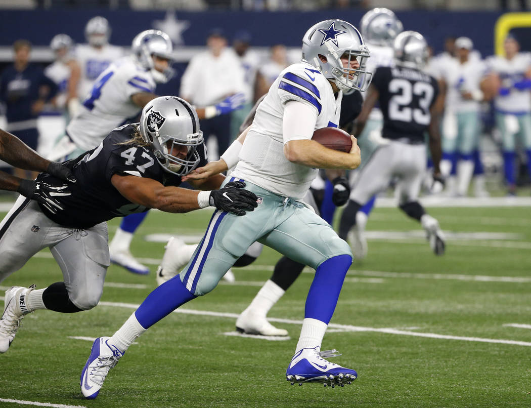 Dallas Cowboys quarterback Cooper Rush (7) runs the ball for a first down as Oakland Raiders linebacker James Cowser (47) attempts the stop in the second half of a preseason NFL football game, Sat ...